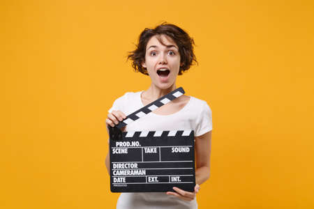 Shocked young brunette woman girl in white t-shirt posing isolated on yellow orange background in studio. People lifestyle concept. Mock up copy space. Hold classic black film making clapperboard.
