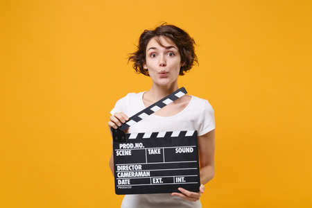 Amazed young brunette woman girl in white t-shirt posing isolated on yellow orange wall background in studio. People lifestyle concept. Mock up copy space. Hold classic black film making clapperboard.