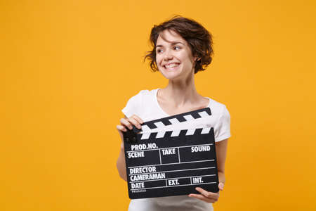 Smiling young brunette woman girl in white t-shirt posing isolated on yellow orange background. People lifestyle concept. Mock up copy space. Hold classic black film making clapperboard looking aside.