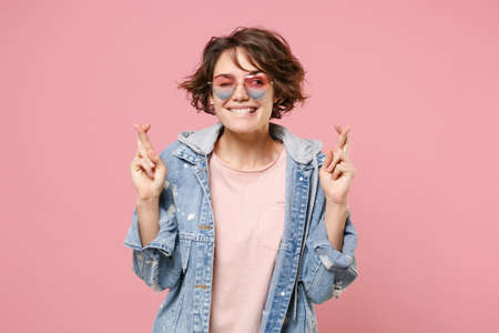 Funny young woman girl in denim jacket, glasses posing isolated on pastel pink background. People lifestyle concept. Mock up copy space. Wait for special moment keeping fingers crossed, making wish. Stock Photo