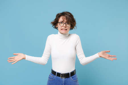 Perplexed puzzled young brunette woman in casual white clothes eyeglasses posing isolated on pastel blue wall background studio portrait. People lifestyle concept. Mock up copy space. Spreading hands.