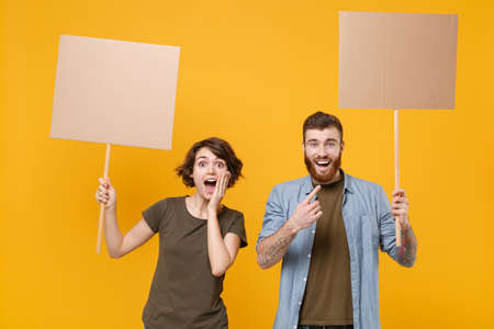 Excited protesting young two people guy girl hold protest signs broadsheet blank placard on stick isolated on yellow background studio portrait. Protests strikes pickets concept. Youth against city.