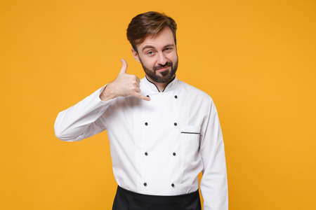 Confident young bearded male chef cook or baker man in white uniform shirt posing isolated on yellow background. Cooking food concept. Mock up copy space. Doing phone gesture like says call me back. Stock fotó
