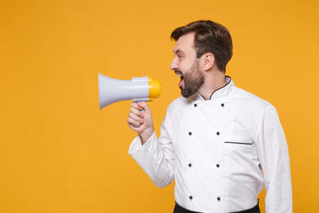 Side view of young bearded male chef cook or baker man in white uniform shirt posing isolated on yellow wall background studio portrait. Cooking food concept. Mock up copy space. Scream in megaphone.