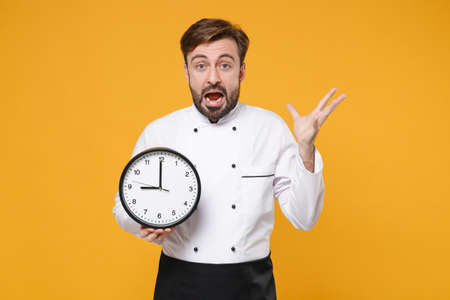 Shocked worried young bearded male chef cook or baker man in white uniform shirt posing isolated on yellow background in studio. Cooking food concept. Mock up copy space. Hold clock, spreading hands. Imagens