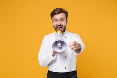 Excited young bearded male chef cook or baker man in white uniform shirt isolated on yellow background. Cooking food concept. Mock up copy space. Scream in megaphone, pointing index finger on camera.