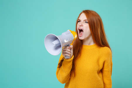 Angry young redhead woman girl in yellow knitted sweater posing isolated on blue turquoise wall background studio portrait. People emotions lifestyle concept. Mock up copy space. Scream in megaphone. Stock Photo