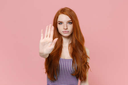 Serious young redhead woman girl in plaid dress posing isolated on pastel pink wall background studio portrait. People emotions lifestyle concept. Mock up copy space. Showing stop gesture with palm. Stock Photo