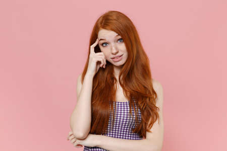 Bewildered young redhead woman girl in plaid dress posing isolated on pastel pink wall background studio portrait. People sincere emotions lifestyle concept. Mock up copy space. Put hand on head.