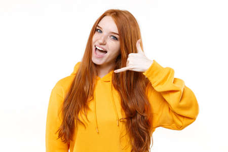 Funny young redhead woman girl in casual yellow hoodie posing isolated on white background studio portrait. People lifestyle concept. Mock up copy space. Doing phone gesture like says call me back.