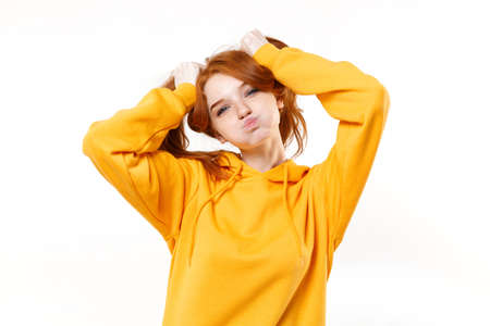 Funny young redhead woman girl in yellow hoodie posing isolated on white background studio portrait. People lifestyle concept. Mock up copy space. Having fun hold hair like ponytails, blowing cheeks.