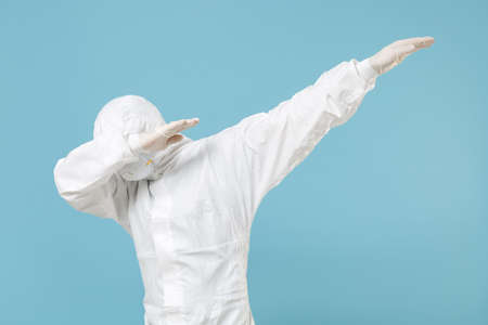 Man in white protective suit respirator mask showing doing DAB dance gesture isolated on blue background studio. Epidemic pandemic rapidly spreading coronavirus 2019-ncov medicine flu virus concept.