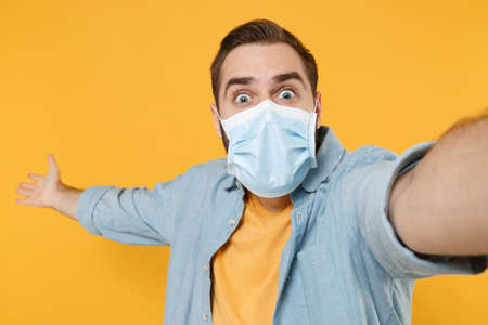 Close up of shocked man in sterile face mask isolated on yellow background. Epidemic pandemic coronavirus 2019-ncov sars covid-19 flu virus concept. Doing selfie shot on mobile phone point hand aside.