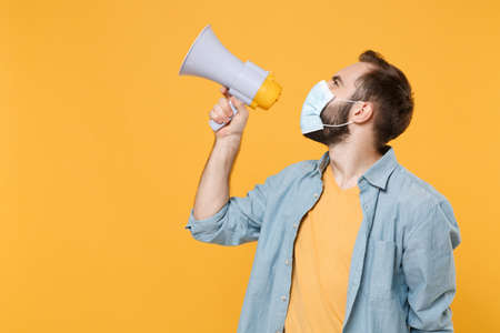 Side view of young man in sterile face mask posing isolated on yellow wall background studio portrait. Epidemic pandemic coronavirus 2019-ncov sars covid-19 flu virus concept. Scream in megaphone.