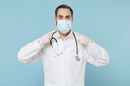 Male doctor man in white medical gown gloves isolated on blue background. Epidemic pandemic spreading coronavirus 2019-ncov sars covid-19 flu virus concept. Point index fingers on sterile face mask.
