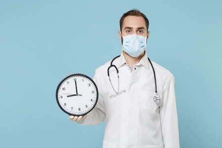 Male doctor man in medical gown sterile face mask gloves isolated on blue background in studio. Epidemic pandemic rapidly spreading coronavirus 2019-ncov sars covid-19 flu virus concept. Hold clock.