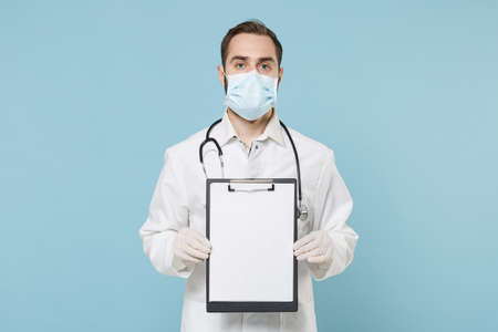 Male doctor man in medical gown face mask gloves isolated on blue background. Epidemic pandemic coronavirus 2019-ncov sars covid-19 flu virus concept. Hold clipboard with blank empty sheet workspace.