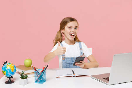 Cheerful little kid schoolgirl 12-13 years old study at desk with laptop isolated on pink background. School distance education at home during quarantine concept. Using mobile phone, showing thumb up. Stock Photo
