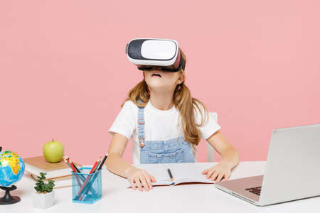 Little kid schoolgirl 12-13 years old sit and study at white desk with pc laptop isolated on pastel pink background. School distance education at home during quarantine concept. Watching in headset. Stock Photo