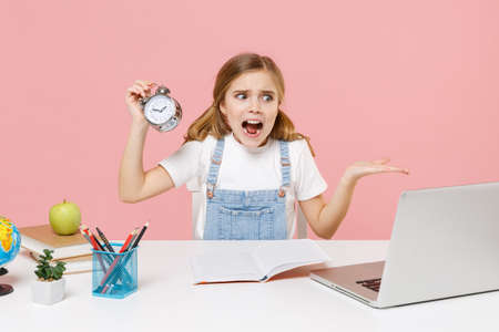 Shocked irritated little kid schoolgirl 12-13 years old study at desk with laptop isolated on pink background. School distance education at home concept. Hold alarm clock, screaming, spreading hands. Imagens