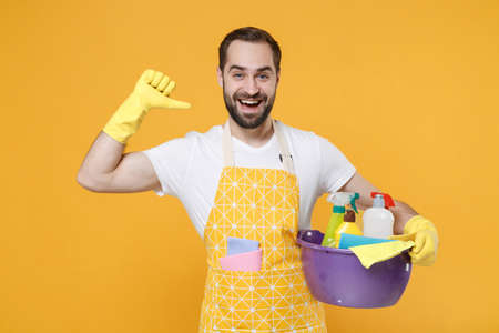 Cheerful man househusband in apron rubber gloves hold basin with detergent bottles washing cleansers doing housework isolated on yellow background studio. Housekeeping concept. Point thumb on himself.