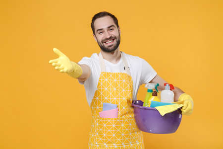 Smiling man househusband in apron rubber gloves hold basin with detergent bottles washing cleansers doing housework isolated on yellow background. Housekeeping concept. Stand with outstretched hand. Banque d'images
