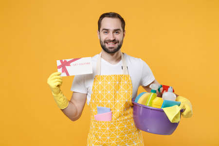 Smiling young man househusband in apron rubber gloves hold basin with detergent bottles washing cleansers doing housework isolated on yellow background. Housekeeping concept. Hold gift certificate. 스톡 콘텐츠