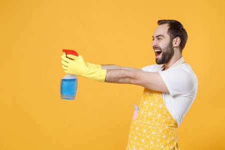 Side view of funny young man househusband in apron rubber gloves hold spray with washing cleanser, cleaning rag while doing housework isolated on yellow wall background studio. Housekeeping concept.