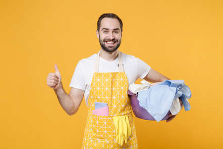 Smiling young man househusband in apron hold basket with clean clothes while doing housework isolated on yellow background studio portrait. Housekeeping concept. Mock up copy space. Showing thumb up.