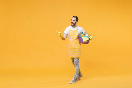 Cheerful young man househusband in apron rubber gloves hold basin detergent bottles washing cleansers doing housework isolated on yellow background. Housekeeping concept. Pointing index finger aside.