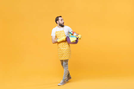 Shocked man househusband in apron rubber gloves hold basin detergent bottles washing cleansers doing housework isolated on yellow background. Housekeeping concept. Mock up copy space. Looking aside.
