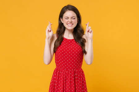 Young brunette woman girl in red summer dress isolated on yellow background. People lifestyle concept. Mock up copy space. Waiting for special moment, keeping fingers crossed eyes closed, making wish. Stock fotó