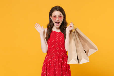 Excited young brunette woman girl in red summer dress, eyeglasses posing isolated on yellow wall background. People lifestyle concept. Hold package bag with purchases after shopping, spreading hands.