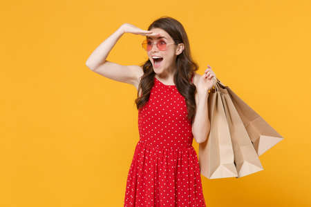 Excited girl in red summer dress, eyeglasses isolated on yellow background. People lifestyle concept. Hold package bag with purchases after shopping, hold hand at forehead looking far away distance.