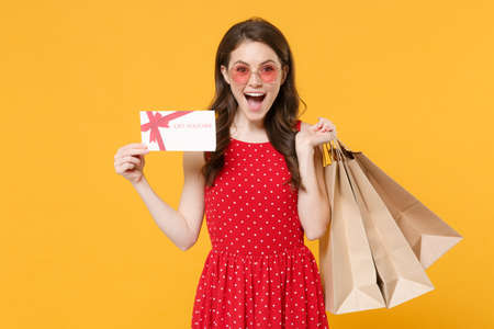 Excited young brunette woman girl in red summer dress eyeglasses posing isolated on yellow background studio. People lifestyle concept. Hold package bag with purchases after shopping gift certificate.