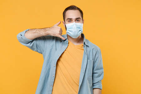 Young man in sterile face mask posing isolated on yellow background studio portrait. Epidemic pandemic rapidly spreading coronavirus 2019-ncov sars covid-19 flu virus concept. Doing phone gesture like says call me back.