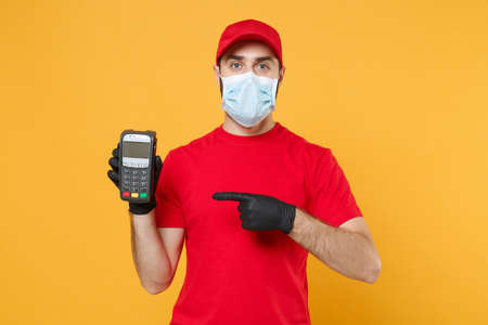 Delivery man in red cap blank t-shirt sterile mask gloves isolated on yellow background studio Guy employee hold bank payment terminal Service quarantine pandemic coronavirus virus 2019-ncov concept Foto de archivo