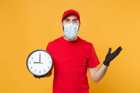 Delivery man in red cap blank t-shirt uniform sterile face mask gloves isolated on yellow background studio Guy employee working courier hold clock Service pandemic coronavirus virus 2019-ncov concept
