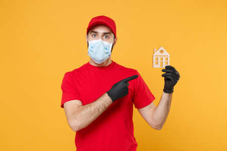 Delivery man in red cap blank t-shirt uniform sterile face mask gloves isolated on yellow background studio Guy employee working courier Service quarantine pandemic coronavirus virus 2019-ncov concept