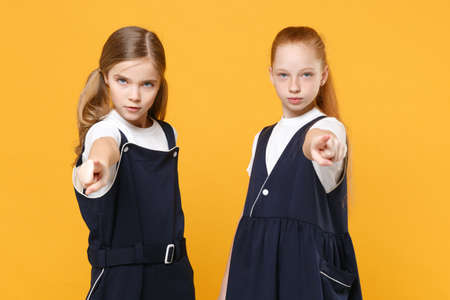 Two young little girls 12-13 years old in white t-shirt blue school uniform dresses isolated on yellow background children studio portrait Childhood kids education lifestyle concept Mock up copy space