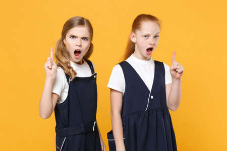 Two young little girls 12-13 years old in white t-shirt blue school uniform dresses isolated on yellow background children studio portrait Childhood kids education lifestyle concept Mock up copy space Foto de archivo
