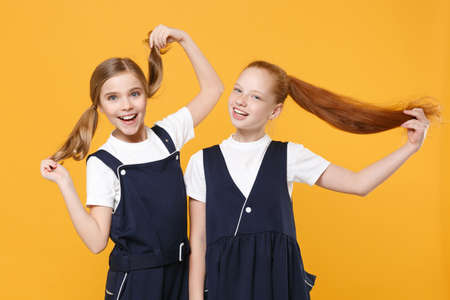 Two young little girls 12-13 years old in white t-shirt blue school uniform dresses isolated on yellow background children studio portrait Childhood kids education lifestyle concept Mock up copy space Standard-Bild