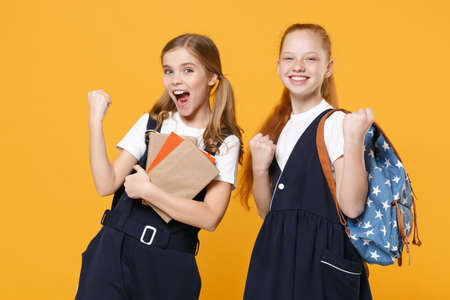 Girls 12-13 years old in white t-shirt blue school uniform dresses hold schoolbooks isolated on yellow background children studio portrait Childhood kids education lifestyle concept Mock up copy space