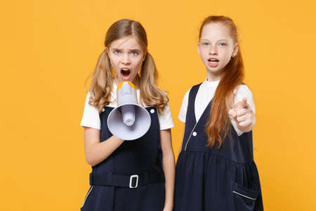 Two fun girls 12-13 years old in white t-shirt blue school uniform dresse scream in megaphone isolated on yellow background children studio portrait Childhood kids education concept Mock up copy space