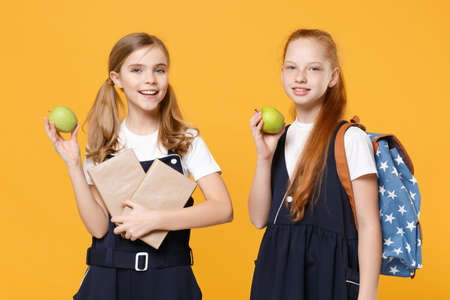 Girls 12-13 years old in white t-shirt blue school uniform dresses hold schoolbooks isolated on yellow background children studio portrait Childhood kids education lifestyle concept Mock up copy space Foto de archivo