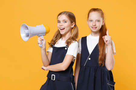 Two fun girls 12-13 years old in white t-shirt blue school uniform dresse scream in megaphone isolated on yellow background children studio portrait Childhood kids education concept Mock up copy space Foto de archivo