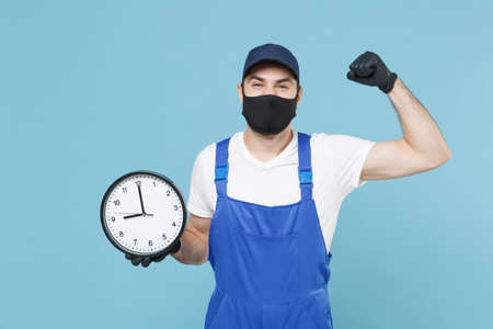 Delivery man in cap t-shirt uniform sterile face mask gloves isolated on blue background studio Guy employee courier hold clock Service quarantine pandemic coronavirus virus covid-19 2019-ncov concept
