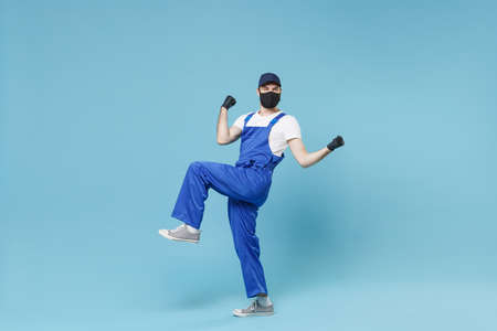 Full length delivery man in cap t-shirt uniform sterile face mask glove isolated on blue background studio Guy employee courier Service quarantine pandemic coronavirus virus covid-19 2019-ncov concept