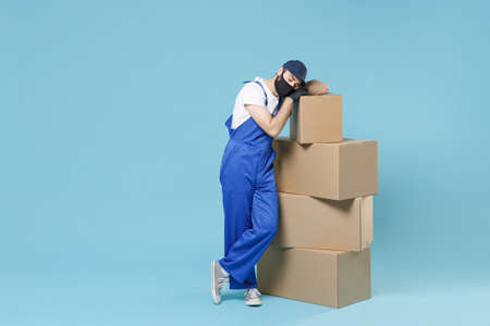 Full length delivery man in cap t-shirt uniform sterile face mask gloves isolated on blue background studio Guy employee courier hold box Service pandemic coronavirus virus covid-19 2019-ncov concept.