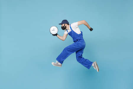 Fun jumping delivery man in cap t-shirt uniform sterile face mask glove isolated on blue background studio Guy employee courier Service quarantine pandemic coronavirus virus covid-19 2019-ncov concept